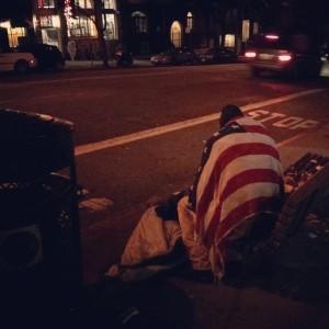homeless man in flag